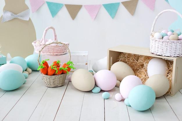 イースター!バニーとバスケットが付いた多くのカラフルなイースターエッグ!部屋のイースター装飾、ゲーム用の子供部屋。ニンジンとウサギのバスケット。巣、卵、干し草の箱。