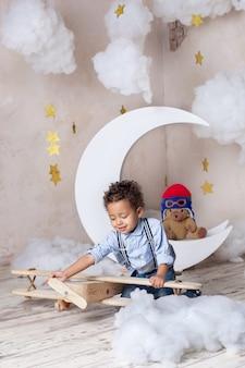 巻き毛のアフリカ系アメリカ人の少年のクローズアップの肖像画。黒人の少年。学校、就学前教育。夢、キャリア。小さな男の子は、幼稚園のエコおもちゃ木製飛行機で遊ぶ。子供の頃、想像力。