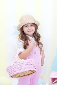 イースター!かわいい女の子が立って、装飾が付いている彼女の手で卵のバスケットを保持しています。かわいい女の子はイースターエッグを探します。イースター装飾、農業。子供と庭。