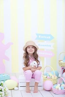 イースター!小さな女の子はイースターのウサギと遊んでいます。子供がイースターのインテリアでウサギを両腕に抱えています。イースターのカラフルな装飾、農業。子供と動物。リトルファーマー。