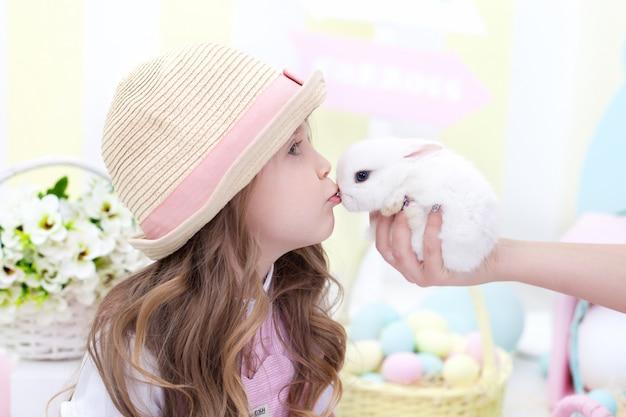 イースター!かわいい女の子はウサギにキスします。イースターのカラフルな装飾。子供はふわふわのウサギと遊ぶ。動物への愛。農業。子供と庭。小さな農家。田舎の動物。アレルギー。春の花