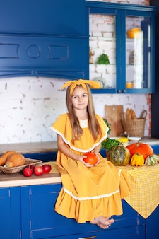 Счастливая маленькая девочка в желтом платье в осеннем декоре с тыквами на кухне,