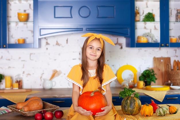 Маленькая девочка сидит на столе в кухне держит большую тыкву. сбор урожая.