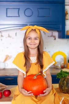 Маленькая девочка сидит на столе в кухне держит большую тыкву.