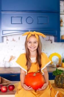 Маленькая девочка держит большую тыкву в кухне дома.