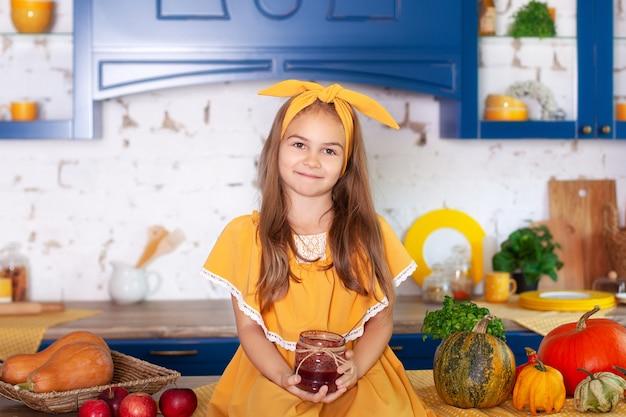 Маленькая девочка, сидя на рабочей поверхности кухни ждет завтрак с банкой варенья. веселый и непослушный ребенок на кухне. интерьер кухни с тыквами, яблоками. здоровое питание. осенний декор