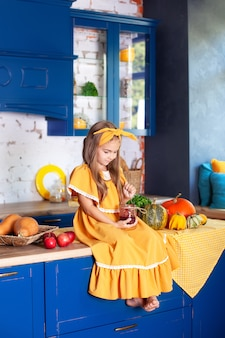 Маленькая девочка сидит на кухонном столе с банкой варенья. веселый ребенок на кухне. маленький повар. интерьер кухни с тыквы, яблоки. здоровое питание. урожай. осенний декор. рустик.