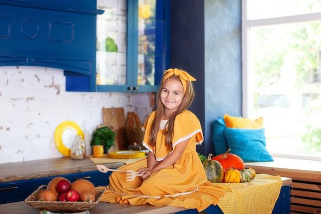 Маленькая девочка сидит на рабочей поверхности кухни в ожидании завтрака. веселая и озорная девушка на кухне. здоровое питание, вегетарианство, витамины, овощи. осенний кухонный декор. простоватый