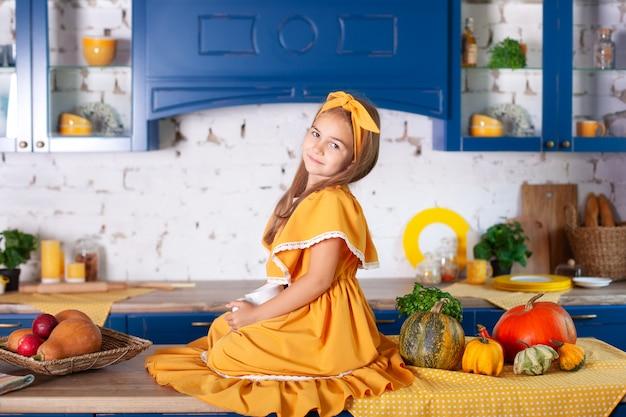 Улыбающийся маленькая девочка, сидя на рабочей поверхности кухни в ожидании завтрака. веселая и озорная девушка на кухне. здоровое питание, вегетарианство, витамины, овощи. осенний кухонный декор