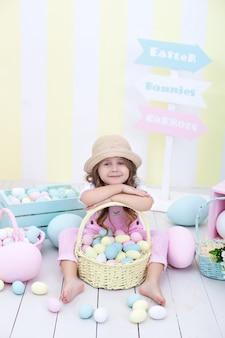 イースター!色とりどりのイースターエッグのバスケットを保持している女の子。イースターのカラフルな家の装飾。イースターエッグを追いかける少女。春の装飾、家族のお祝い。小さな農家。収穫。ファーム。イースターのインテリア