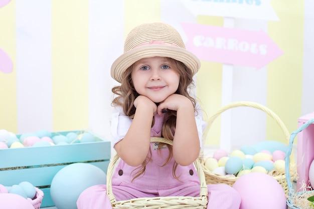 イースター!女の子はイースターインテリアに卵のバスケットを保持しています。イースターのカラフルな装飾。イースターエッグを追いかける少女。春の装飾、家族のお祝い、農業。子供と庭。収穫