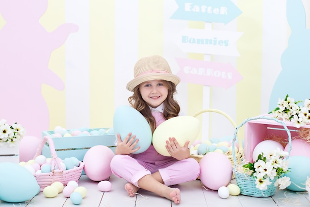 イースター!女の子はイースターのインテリアに彼女の手で大きなマルチカラーの卵を保持しています。かわいい赤ちゃんがイースターエッグを追いかけています。イースター装飾。子供と庭。小さな農家。収穫