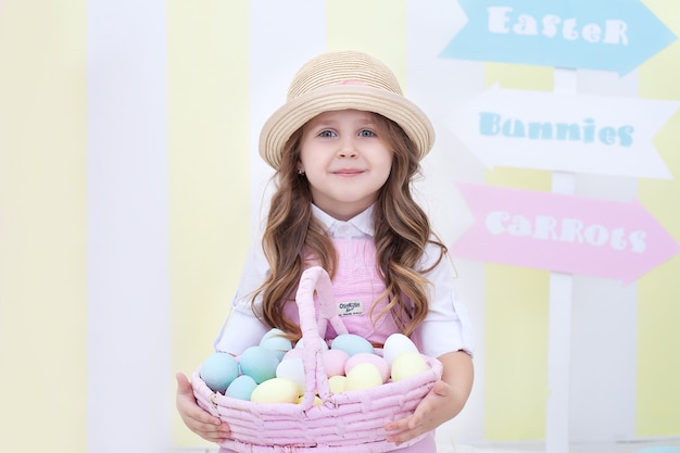 イースター!小さな女の子はイースターインテリアに卵のバスケットを保持しています。イースターのカラフルな装飾。少女は塗装卵の入ったバスケットを持っています。農業。子供と庭。