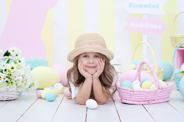 イースターの家でカラフルな装飾。塗装卵付きバスケット近くの女の子。小さな女の子はイースターエッグを探します。女の子には塗装卵のバスケットがあります。リトルファーマー。春の装飾。イースターのインテリア。子供部屋