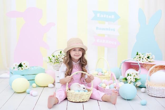 イースターのコンセプト!小さな女の子はバスケットでイースターのウサギと遊んでいます。イースターの家でカラフルな装飾。イースターのインテリアにカラフルな塗装卵のバスケットにふわふわのウサギ。
