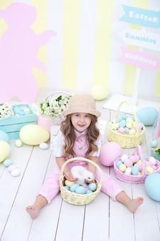 イースター!小さな女の子はバスケットでイースターのウサギと遊んでいます。イースターの家でカラフルな装飾。イースターのインテリアにカラフルな塗装卵のバスケットにふわふわのウサギ。春