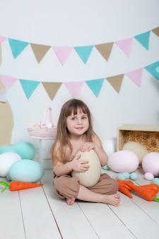 イースター!イースターのカラフルな卵、イースターバスケット、ノウサギと白い壁に美しい少女。イースターの装飾、春の装飾の家。家族の休日、伝統。収穫、小さな農家。