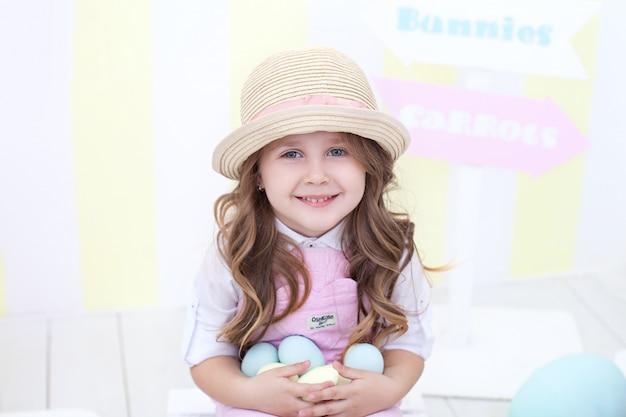 イースター!微笑んでいる女の子は、イースターのインテリアでカラフルな卵をたくさん手に持っています。子供の手の中のマルチカラーのイースターエッグ。小さな農家。子供と庭。
