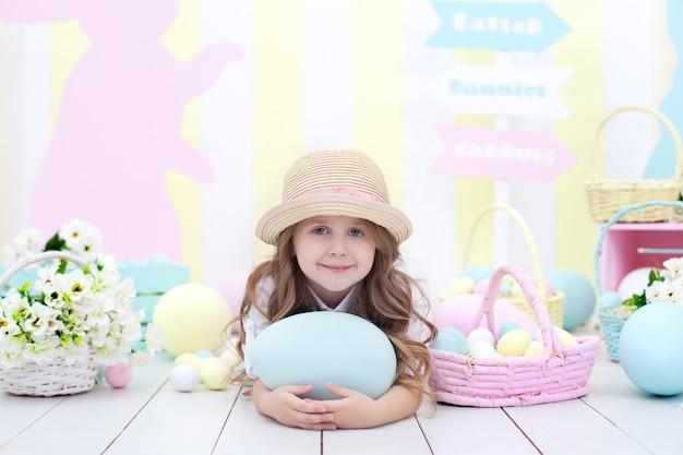 イースター!イースターエッグと遊ぶかわいい女の子。子供はイースターのインテリアに大きなカラフルな卵を保持しています。 。春の部屋のインテリア