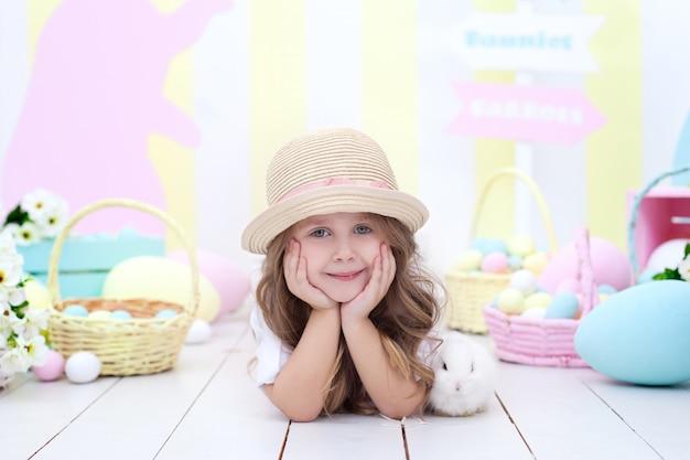 イースター!小さな女の子はイースターのウサギと遊んでいます。イースターのカラフルな装飾、カラフルな卵のバスケット。イースターエッグを追いかけて赤ちゃん。農業。子供と庭。小さな農家。ふわふわウサギと遊ぶ子供