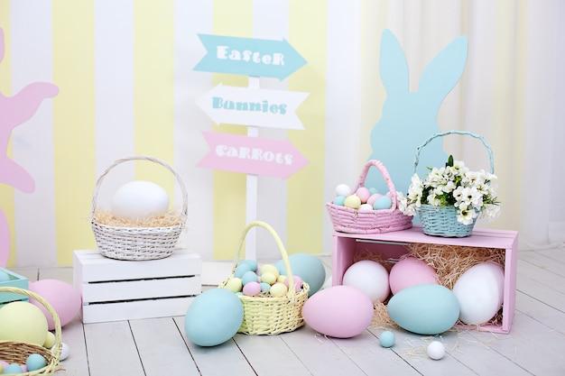 イースター!カラフルなイースターの部屋のインテリア。バニーと花のバスケットが付いた多くのカラフルなイースターエッグ!子供用プレイルーム。春の部屋の装飾とイースターの装飾。春の家の装飾と春の花