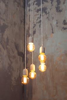Многие различные старинные лампочки, свисающие с потолка. лофт подвесные светильники с грубой цементной штукатуркой на стене. минимальный чердак интерьер. современные лампочки эдисона. лампочки в винтажном стиле.