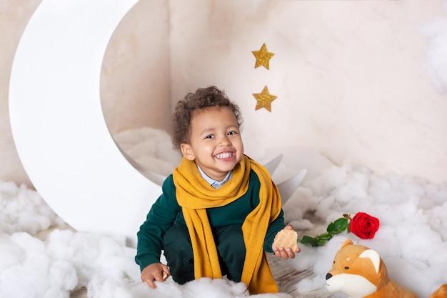 アフリカ系アメリカ人の少年の顔のクローズアップの肖像画。小さな男の子が座って笑顔します。かわいい赤ちゃん、ゲームの赤ちゃん。可愛い笑顔。巻き毛。子供時代。子供は幼稚園で遊ぶ。幼児教育