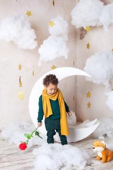 バラと小さな黒い男の子。祝日おめでとうございます。子供の想像力。少し巻き毛のアフロアメリカン。休日の概念。