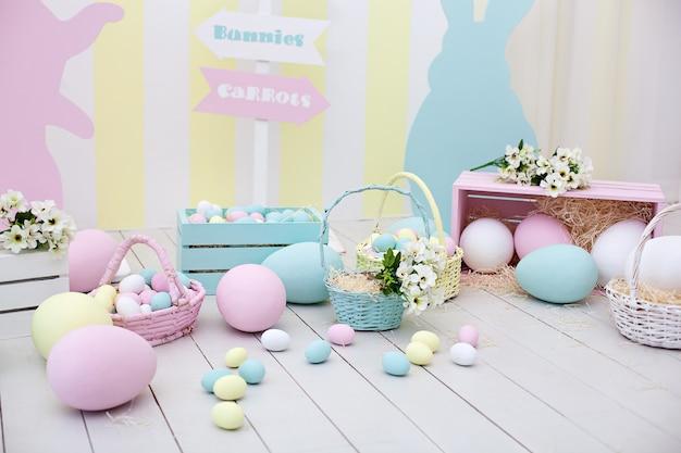 イースター!バニーと花のバスケットが付いた多くのカラフルなイースターエッグ!イースタールームの装飾と装飾、子供用プレイルーム。大小の塗装イースターエッグとカラフルなウサギ。春の家の装飾
