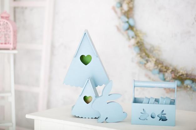 青のスタイリッシュな家の装飾は、木製のバスケット、装飾的な入れ子箱、かわいいウサギです。イースターデコレーション。白いテーブルの上の木製のネストボックスと夏の村の構成。春の部屋の装飾