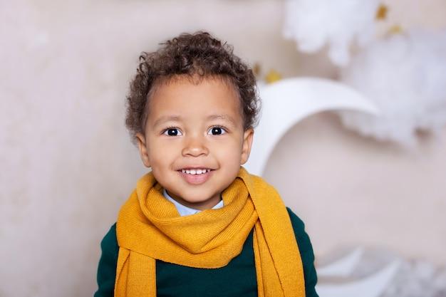 黒人少年をクローズアップ。黄色のスカーフで陽気な笑みを浮かべて黒少年の肖像画。少しのアフリカ系アメリカ人の肖像画。黒人の男。物思いにふける子。子供時代。子供は幼稚園で遊ぶ。小さな男の子の顔