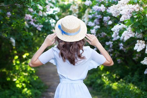 春の午後に青いリボンと麦わら帽子の少女。背面図。トレンディなカジュアルな夏または春の装い。船頭の麦わら帽子の女性。女性の春のファッションのコンセプト。開花ライラックの茂み
