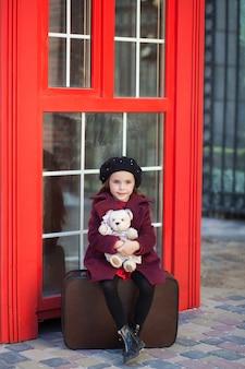小さな女の子はテディベアとスーツケースに座っています。ロンドンの赤い電話ボックス。春。秋。旅。ロンドン、イギリス。春。女子高生。学校の休憩。ベレー帽とコートの少女