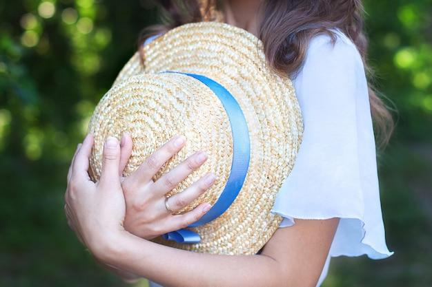 女の子は夏の日に手に青いリボンの付いた麦わら帽子をかざしています。