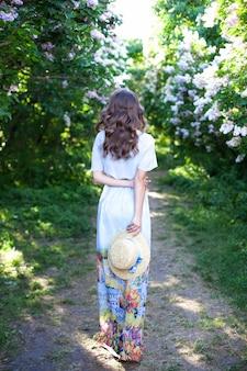 春の午後に青いリボンと麦わら帽子の少女。背面図。トレンディなカジュアルな夏または春の装い。ストリートファッション。船頭の麦わら帽子の女性。女性の春のファッションのコンセプト