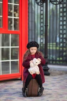 小さな女の子はテディベアとスーツケースに座っています。ロンドンの赤い電話ボックス。春。秋。トリップ。旅。ロンドン、イギリス。女子高生。学校の休憩。ベレー帽とコートの少女。旅行