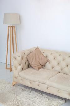 広々とした白いリビングルームの装飾的な枕とランプとベージュのソファ。白い壁に快適なソファのある部屋のインテリア。室内装飾。北欧スタイルのインテリア。心地よさの概念