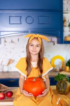 Маленькая девочка держит большую тыкву в кухне дома. сбор урожая. здоровое питание, вегетарианство, витамины, овощи.