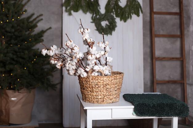 かごの中の綿の花。スカンジナビア。繊細な白い綿の花。家の内部の綿の花。テーブルの上のバスケットに乾燥した白いふわふわの綿。素朴なインテリア。クリスマス。新年。