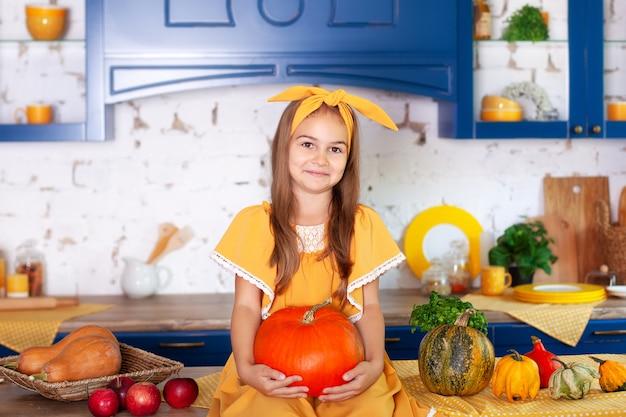 Маленькая девочка сидит на столе в кухне держит большую тыкву. сбор урожая. здоровое питание, вегетарианство, витамины, овощи.