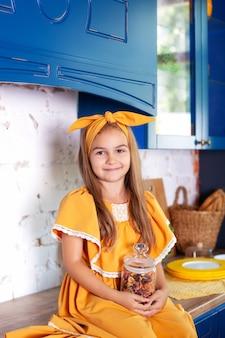 Маленькая девочка в желтом платье держит банку сырой пасты на стене кухни дома. маленький повар. концепция здорового питания. ребенок готовит пасту. концепция приготовления пищи. рустик. скандинавия