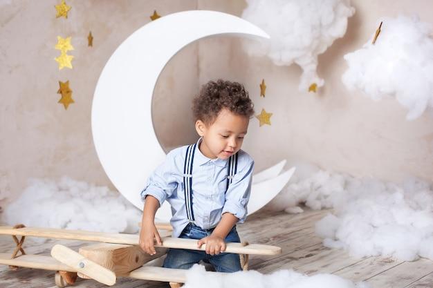 アフリカ系アメリカ人の少年。黒人の少年。学校、就学前教育。夢、キャリア。小さな男の子が木製の飛行機のおもちゃで遊んでいます。子供の頃、想像力。子供が幼稚園でエコおもちゃを遊ぶ