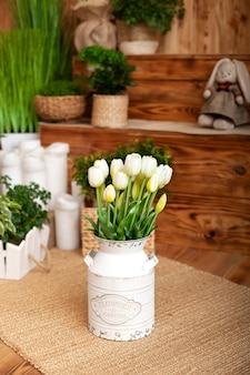 Букет белые тюльпаны цветы в корзине. интерьер весеннего двора. деревенская терраса. крупный план цветочных горшков с заводами. молодые растения, растущие в саду. весеннее украшение, тюльпаны в корзине. пасхальный