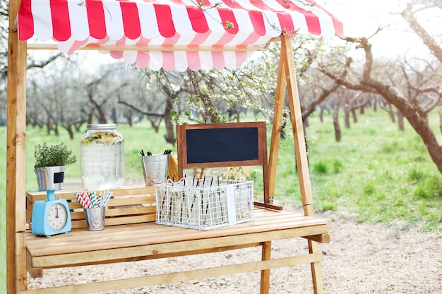 緑の芝生の公園には、レモネードのある木製のカウンターがあります。愛らしい夏のレモネードスタンド。庭で自家製レモネードを調理します。オープンエアの木製のスタンドにガラスの瓶でレモネード
