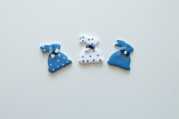 Пасхальные кролики печенье. застекленные пряники пасхи на деревянный стол. домашнее пасхальное печенье в форме забавного кролика. праздничное оформление. творческое печенье пасхи на изолированной белой стене.