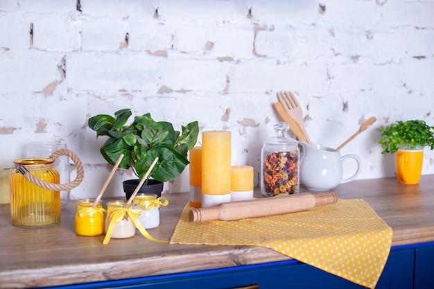 木製のテーブルの様々な台所用品。家の装飾のキッチンのコンセプトです。キッチンツール、キャンドル、白いレンガの壁に木製の麺棒。カラフルなパスタの瓶。春のキッチンのインテリア。イースター