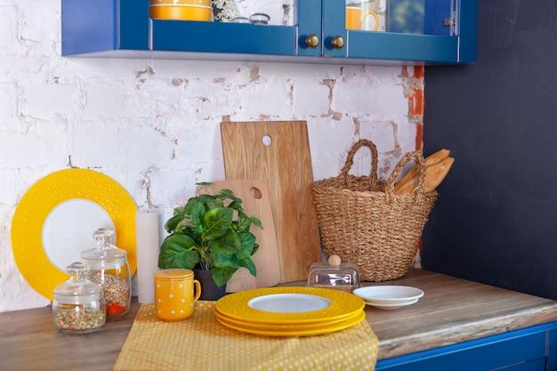 キッチン用品、家の装飾キッチンのコンセプト。調理器具と清潔な食器を備えたモダンなキッチン。キッチンツール、白いレンガの壁にテーブルの上のまな板。ダイニングインテリア。素朴な