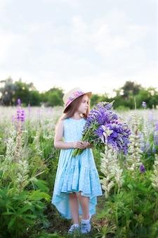 Маленькая красивая девушка в соломенной шляпе и платье в поле люпинов. девушка держит большой букет фиолетовых люпинов в цветущем поле. концепция детского и летнего отдыха. природа и романтика.