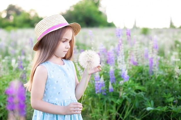 Красивая маленькая девочка, стоя на цветущем поле в зеленой траве и держит одуванчик. наслаждайся природой. здоровая улыбающаяся девочка на летней лужайке. аллергия без понятия. детство. копировать пространство