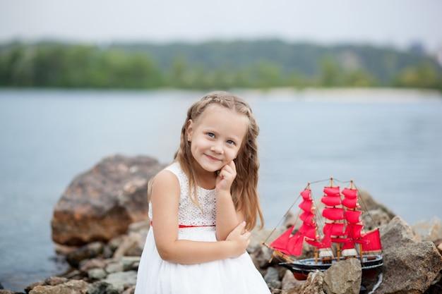 クローズアップの肖像画白いドレスと赤い帆のかわいい女の子。子供がおもちゃの船で海の上に座ります。子供の頃のコンセプトです。ビーチの砂のゲーム。残りの概念。子供が屋外でおもちゃで遊ぶ